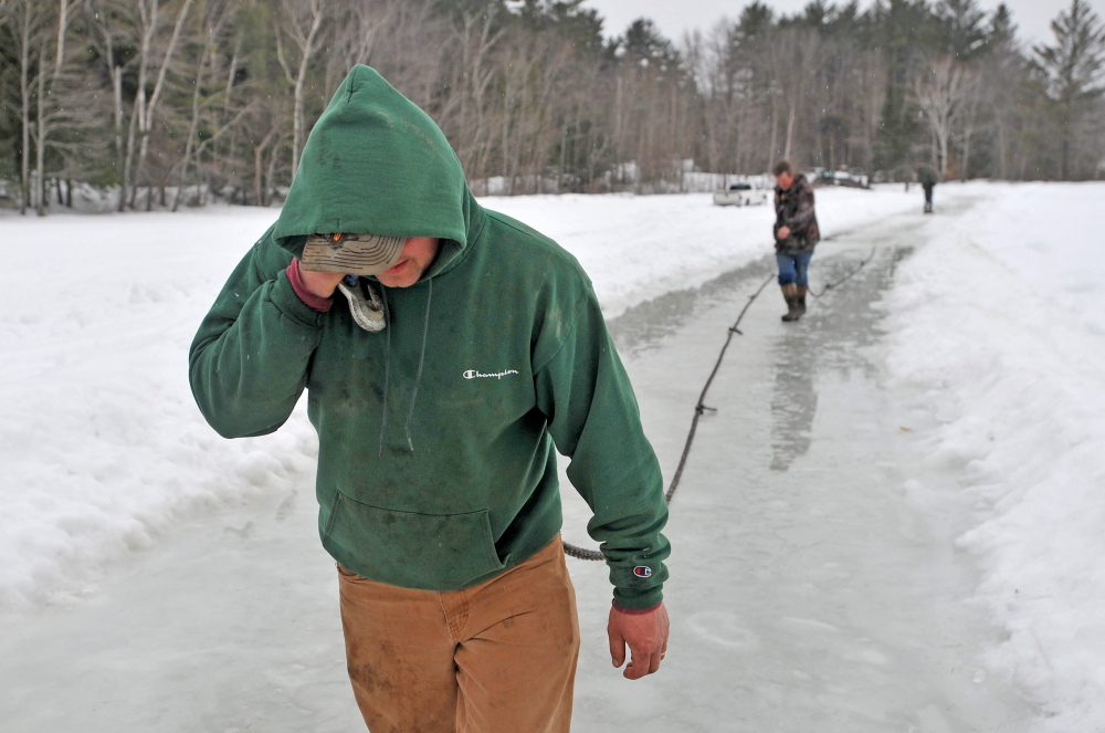 SOFT ICE: Steve Richardson, foreground, and Dave Richardson lay out nearly a quarter-mile of ropes and chains from Roger Hodgdon's flatbed wrecker on Friday in a attempt to haul a stuck pickup truck from the broken ice at Lake George in Canaan. Richardson's truck broke through about 2 feet of ice, coming to rest on another layer of ice and lake water as they were trying to clear their ice fishing shack from the lake ahead of an April 1 deadline.