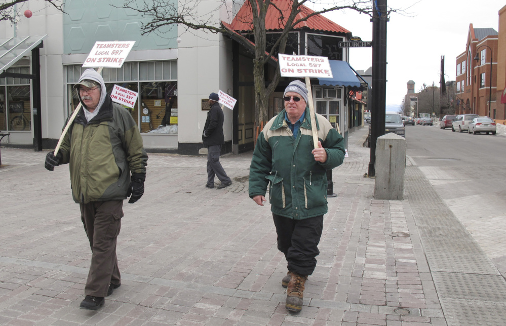 Striking bus drivers Rick LaFerriere, left, and Derek Lorrain walk a picket line Wednesday in Burlington, Vt. The strike continued into a second week, leaving thousands of people scrambling to find ways to get to work, school and appointments.
