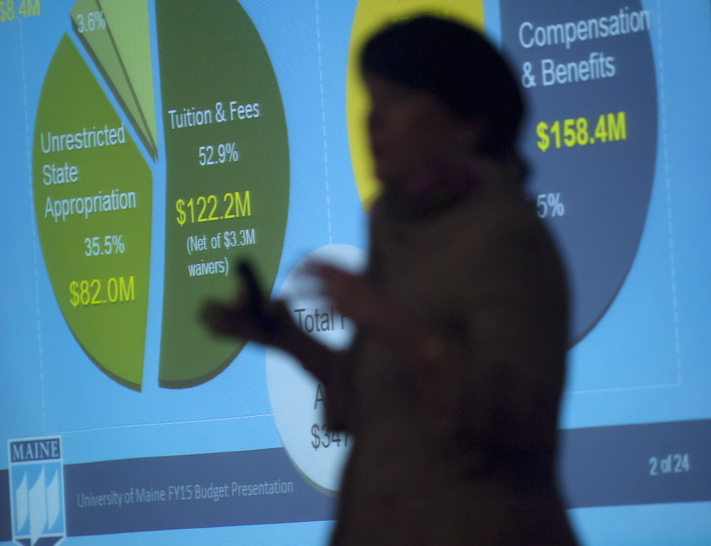 Janet Waldron, University of Maine's senior vice president for administration and finance, is silhouetted in front of an overhead display during a budget presentation in Orono on Friday.