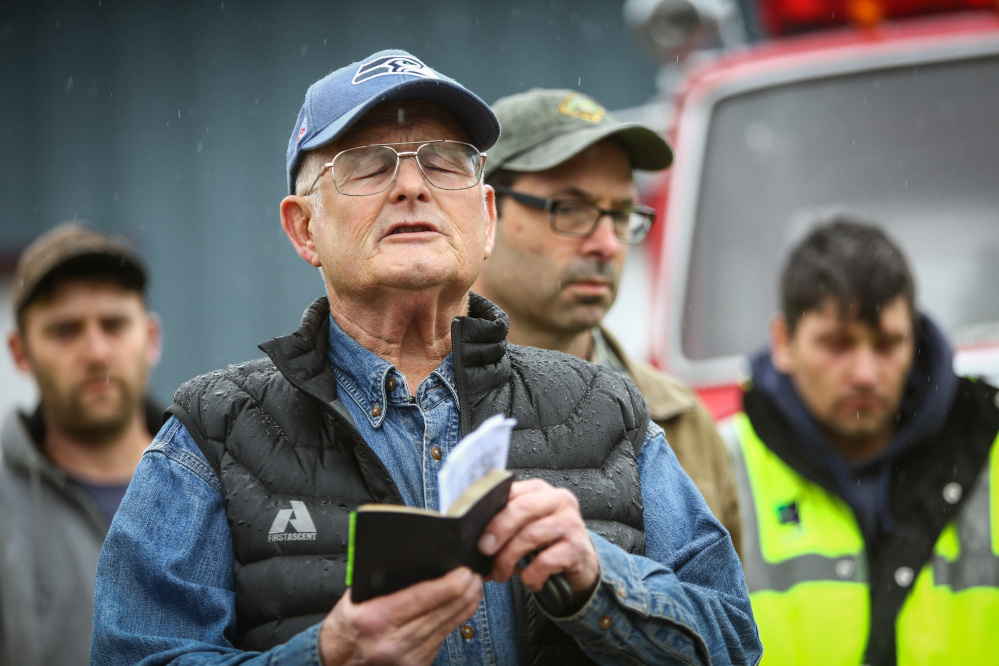 The Rev. Michael De Luca offers a prayer before a statewide moment of silence to honor the victims of the Oso mudslide Saturday in Darrington, Wash.
