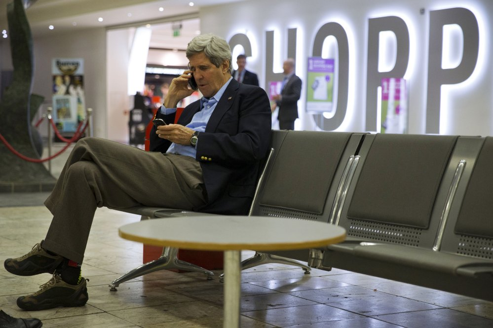 U.S. Secretary of State John Kerry speaks on his phone at Shannon Airport in Ireland on Saturday during a refueling stop. Halfway home from Saudi Arabia, Kerry has abruptly changed course and will stay in Europe for talks on the Ukraine crisis.