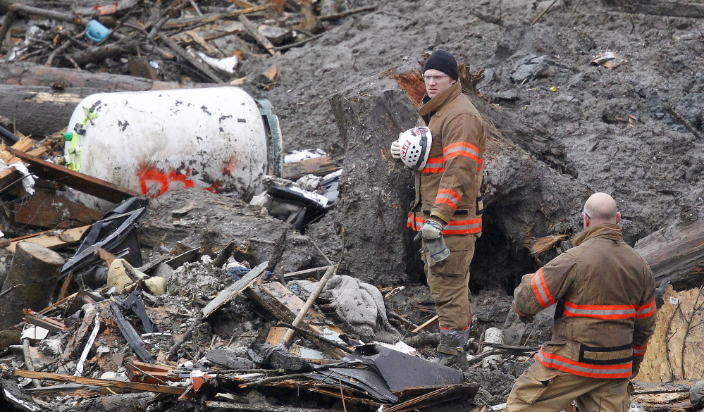 Searchers pause for a moment of silence Saturday at the scene of the mudslide in Oso, Wash.