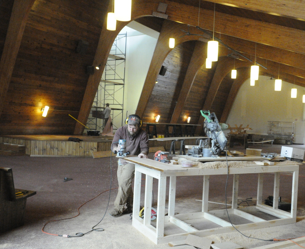 From sitting to standing: Jon Avery runs a router around a board from an old pew that he is turning into a stair tread March 22 at the new Kennebec Community Church in Augusta. Avery, a pastoral intern, said the stage behind him had been built from the former Catholic church's pews.