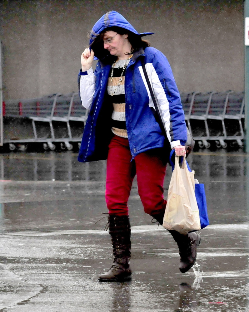 "Staff photo by David Leaming LIQUID SNOW: Sarah Wright leans into the blowing rain and shields her face with a hood at Elm Plaza inWaterville on a wet Sunday, March 30, 2014. ""This rain is better than snow,"" wright said."