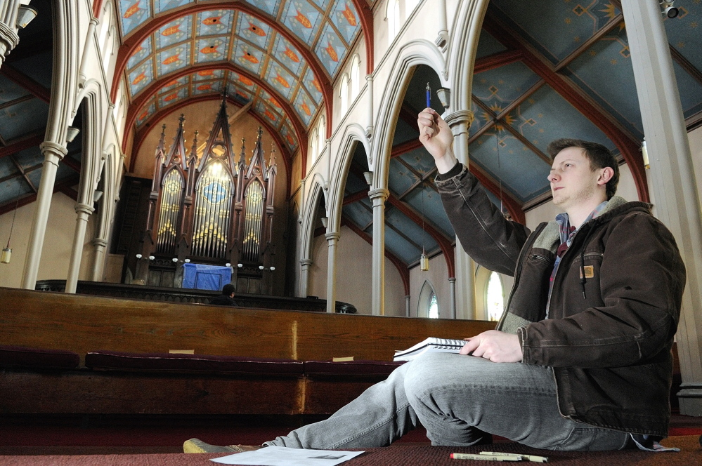 Ben Bailey, of Farmington, lines up his pencil to measure the wall inside South Parish Congregational Church on Thursday.
