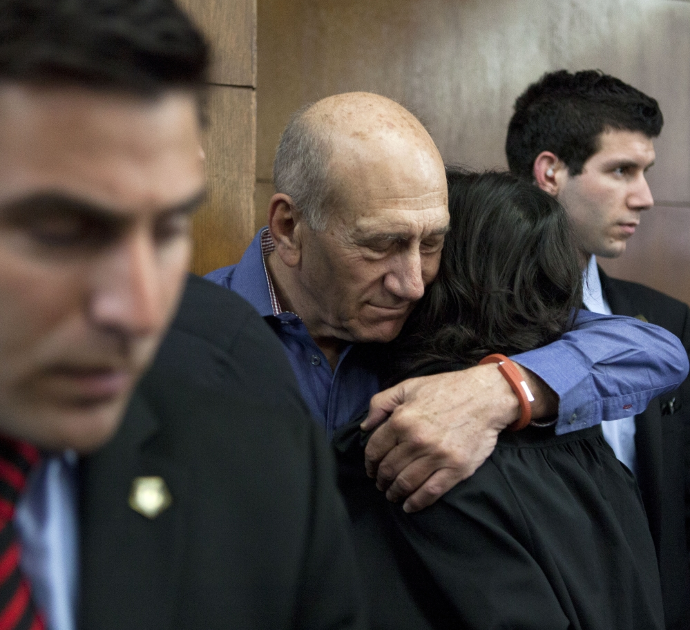 Former Israeli Prime Minister Ehud Olmert hugs a friend before a hearing at Tel Aviv's District Court on Monday. Olmert was convicted in a high-profile bribery case.