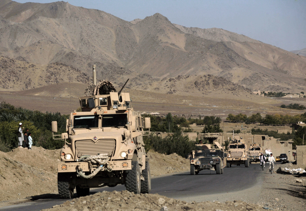 A column of U.S. Army Mine Resistant Ambush Protected armored vehicles – MRAPs – and Afghan National Army vehicles pass through a village during a joint patrol in the Jalrez Valley in Afghanistan's Wardak Province in this 2009 file photo.
