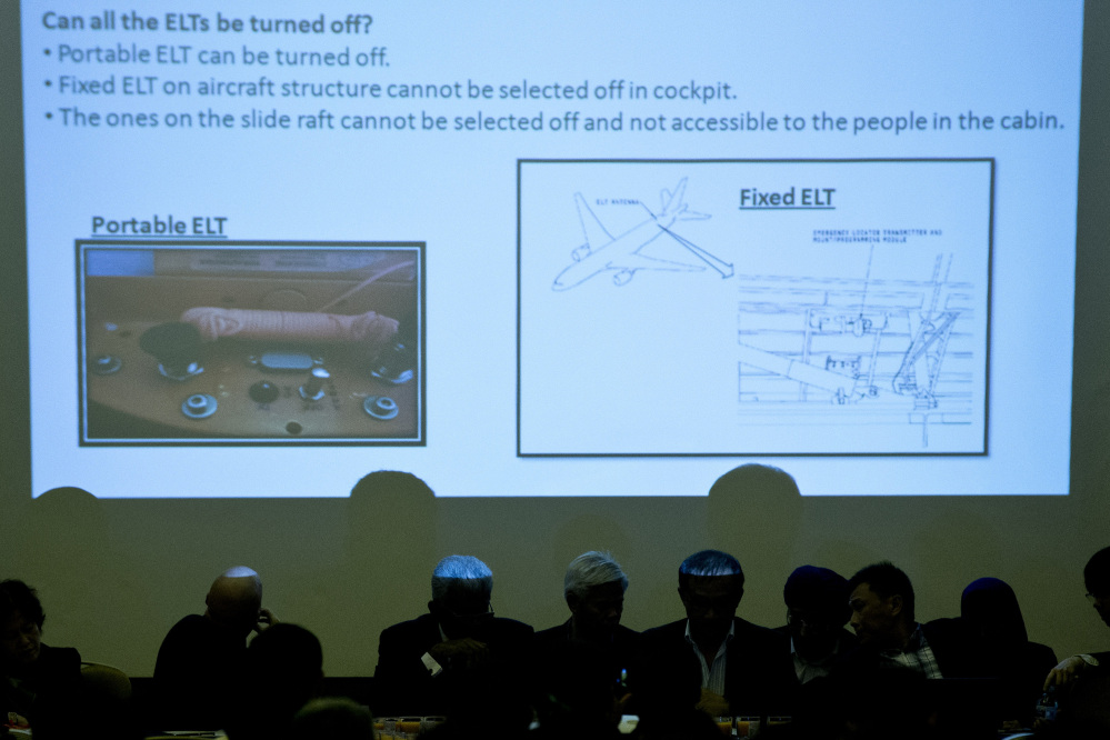 Malaysian officials attend a presentation in Beijing on Monday for the relatives of Chinese passengers onboard Malaysia Airlines Flight 370. Pictures of emergency locater transmitters are being shown during the presentation.
