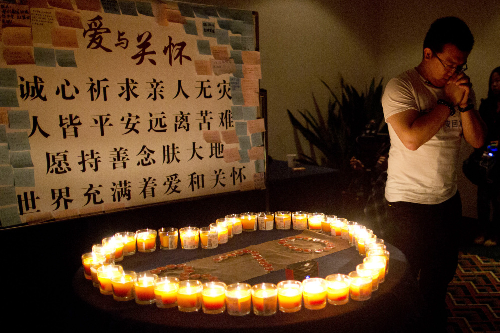 A man, one of the relatives of Chinese passengers onboard Malaysia Airlines Flight 370, prays near candles before a briefing with Malaysian officials at a hotel in Beijing, China, Monday, March 31, 2014.
