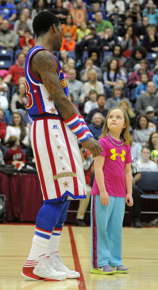 Staff photo by Andy Molloy Suzie Webster, 7, of Winthrop teaches Harlem Globetrotter Bull Bullard a move during a match Monday in Augusta.