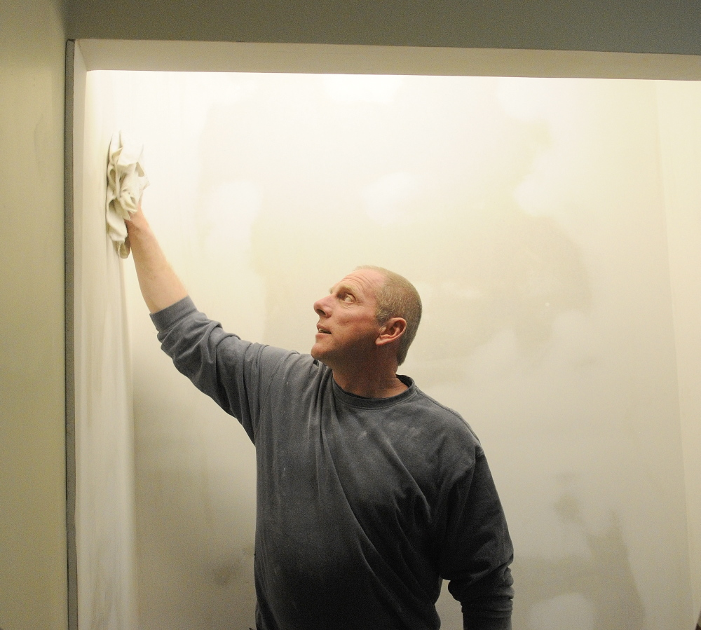 FOR PETS AND AMY: After sanding the wall, Steve Gayne, owner of S n S Multitasking, wipes off dust before painting a wall in the room he is renovating for the Amy Buxton Pet Pantry at South Parish Congregational Church in Augusta.