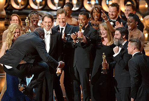 """Director Steve McQueen, left, celebrates with the cast and crew of """"12 Years a Slave"""" as they accept the award for best picture during the Oscars at the Dolby Theatre in Los Angeles on Sunday."""