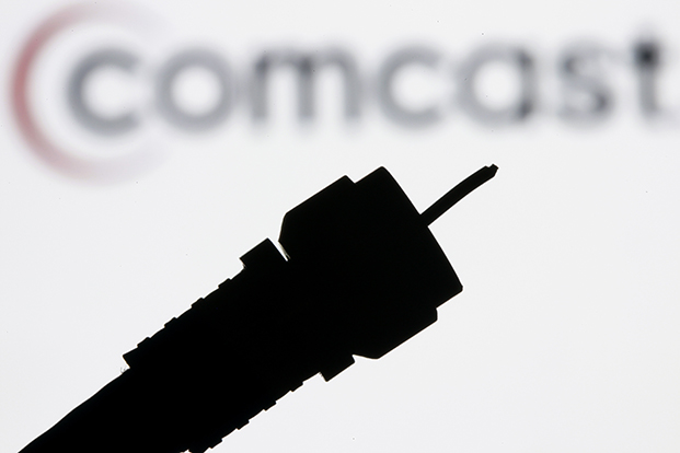 In this July 30, 2008 file photo illustration, a silhouetted coaxial cable is photographed with the Comcast Corp. logo in the background in Philadelphia.