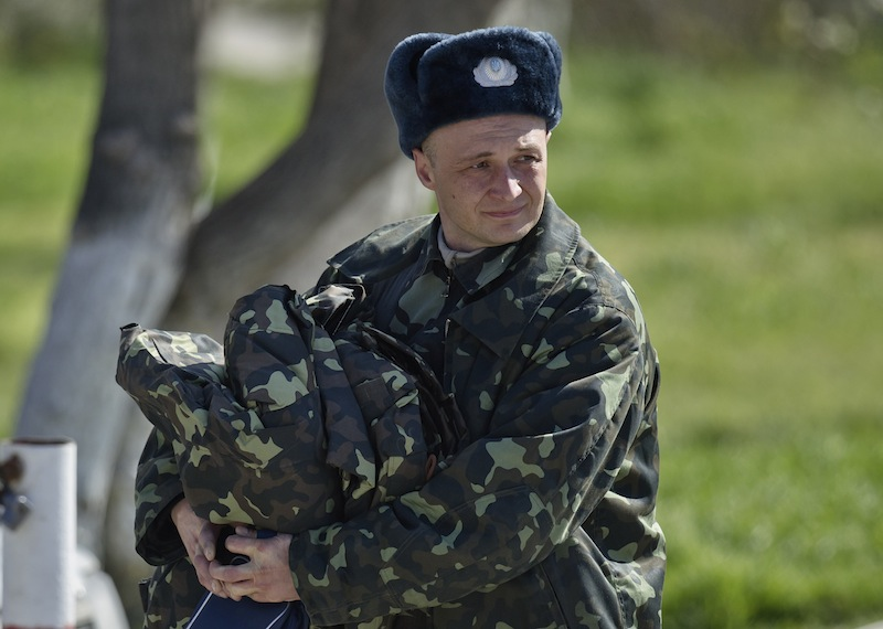A Ukrainian airman carries belongings as he leaves the Belbek air base, outside Sevastopol, Crimea, Friday, March 21, 2014. The base commander Col. Yuliy Mamchur said he was asked by the Russian military to turn over the base but is unwilling to do so until he receives orders from the Ukrainian defense ministry.