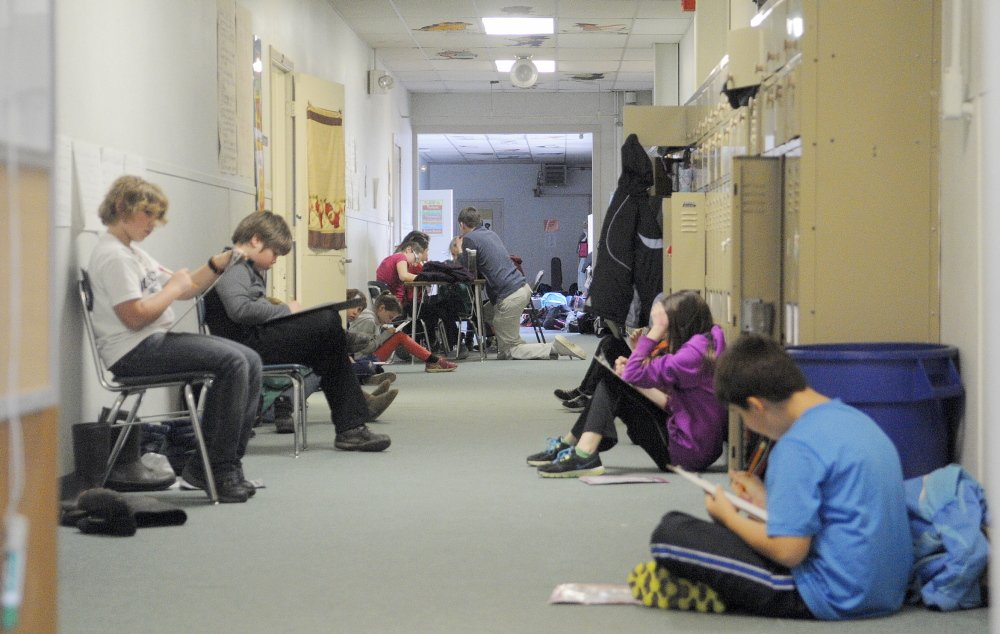 Space Issues: Students work in a hallway Thursday at the Monmouth Middle School. The school has been added to a state list for renovation.