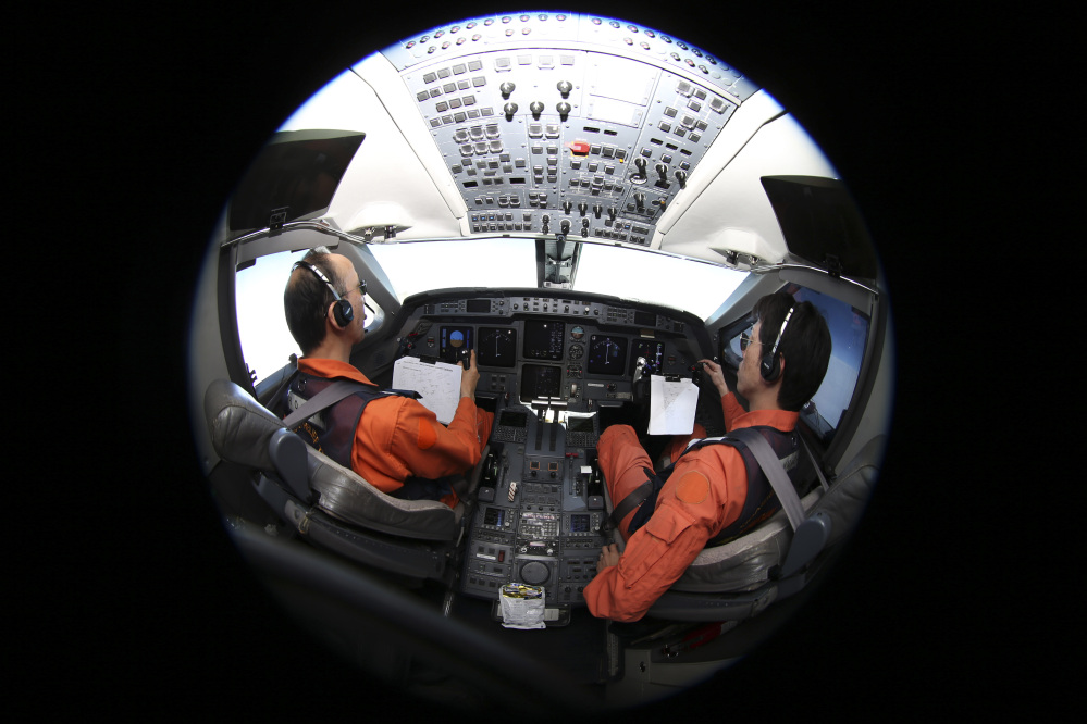Captain of the Japan Coast Guard Gulfstream Makoto Hoshi left, and his co-pilot Shunichi Yumiza sit in the cockpit during a search for the missing Malaysia Airlines Flight MH370 in Southern Indian Ocean, near Australia, Tuesday.