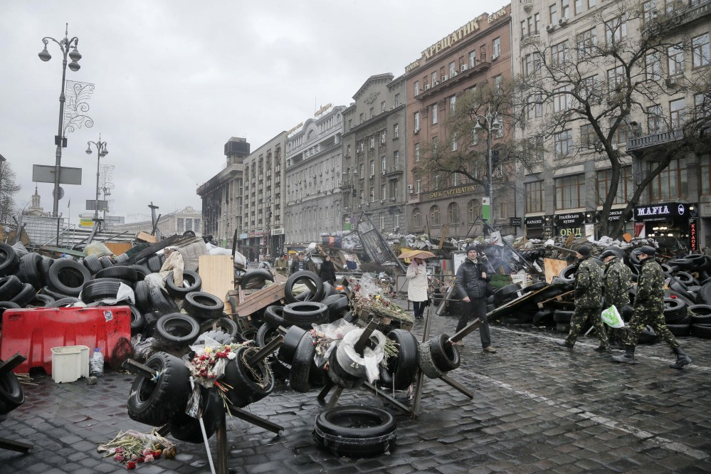 People pass barricades near the Dnipro Hotel in Kiev, where a tense standoff between Ukrainian police and a radical nationalist group Right Sector ended Tuesday when its members surrendered their weapons. Their departure followed a shooting spree in which a Right Sector member shot and wounded three people, including a deputy mayor, outside a restaurant adjacent to the capital's Independence Square.