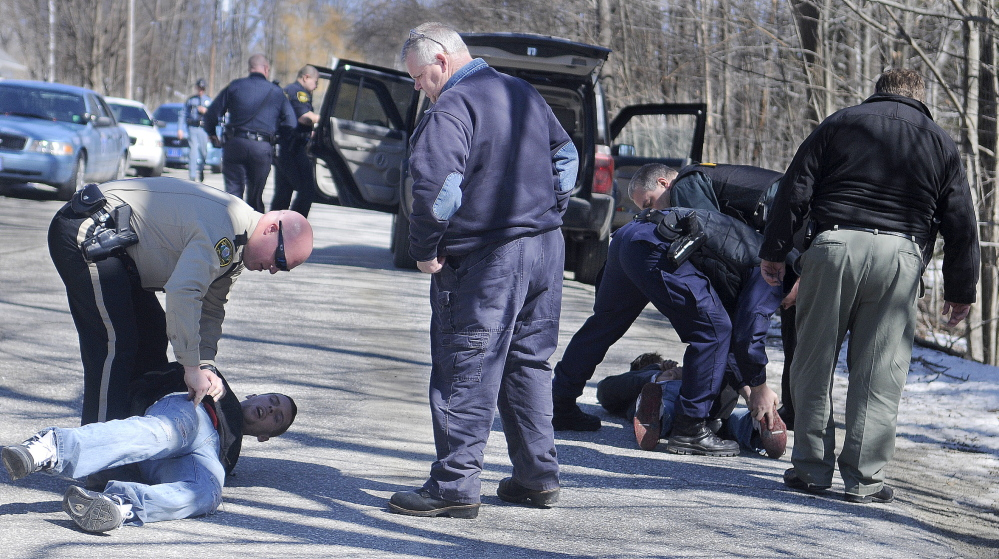 TWIN ARRESTS: Police handcuff and search two men Tuesday morning on Harrison Avenue in Gardiner.