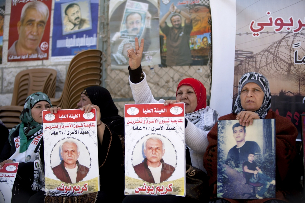 """Women hold portraits of Palestinian prisoners held in Israeli jails during a rally calling for their release in the West Bank city of Ramallah on Tuesday. Arabic on the posters reads, """"Dean of prisoners, Karim Younis, 21 years in prison."""""""