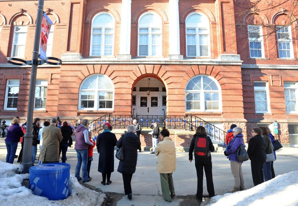 Staff photo by Michael G. Seamans People gather to listen to Chief Joseph Massey of the Waterville police department speak at a child abuse awareness rally at Castonguay Square in Waterville on Wednesday.