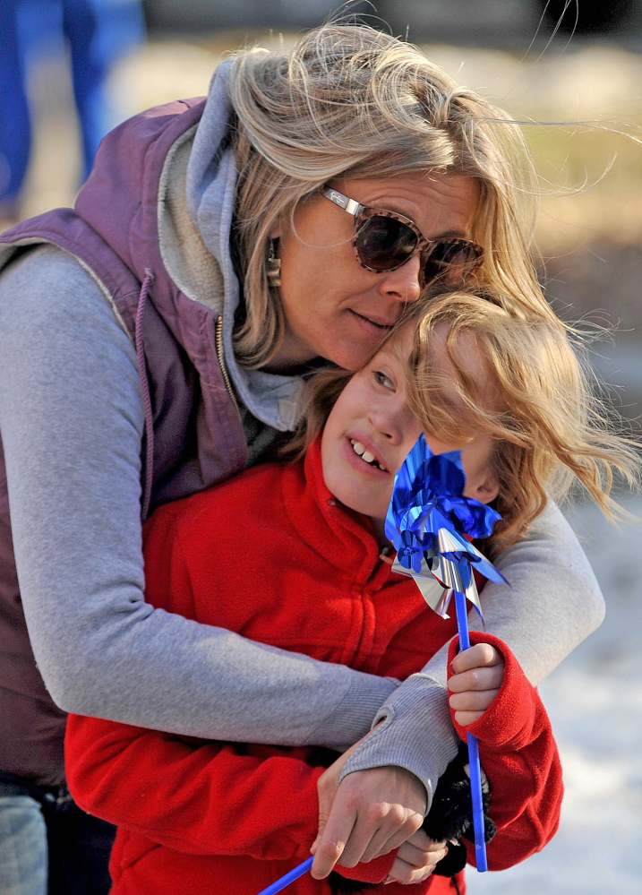 Staff photo by Michael G. Seamans Morrigan Knox-McLeod cuddles with her daughter Ava Doody-McLeod, 7, during the child abuse awareness rally at Castonguay Square in Waterville on Wednesday.