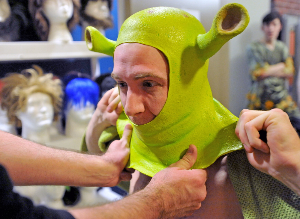 Staff photo by Michael G. Seamans Dan Kennedy gets help with his Shrek costume from costume and hair designer, Kurt Alger, as the cast prepares for the first dress rehearsal of Shrek the Musical at the Waterville Opera House on Wednesday. Shrek the Musical will be playing various dates from April 4 to 13.