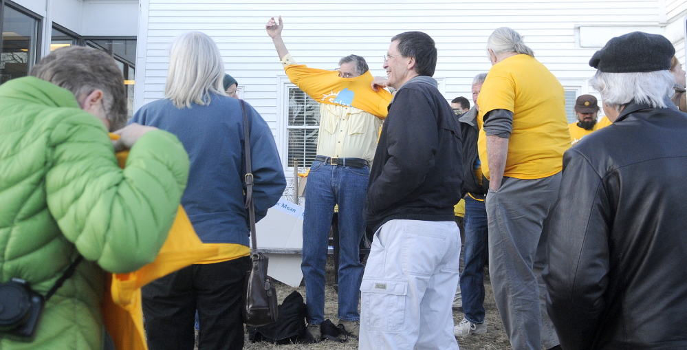 Staff photo by Andy Molloy FIGHT THE POWER: Supporters of solar energy put on yellow t-shirts Wednesday outside of the Public Utility Commissions offices in Hallowell before a hearing for Central Maine Power's request for a rate increase. About two dozen people attended the gathering.