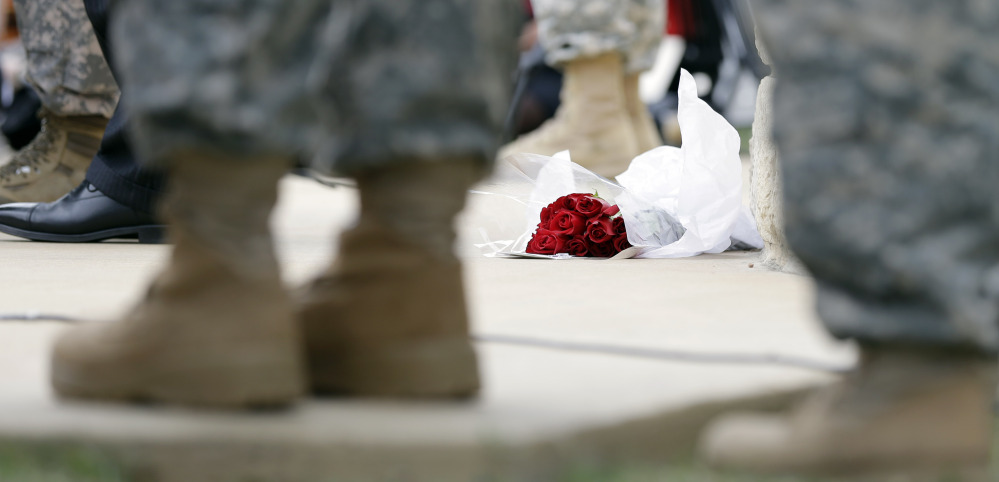 Roses left for shooting victims are seen at the feet of Lt. Gen. Mark Milley, U.S. Sen. John Cornyn, and other military during a news conference near Fort Hood's main gate, Thursday, April 3, 2014, in Fort Hood, Texas. A soldier opened fire Wednesday on fellow service members at the Fort Hood military base, killing three people and wounding 16 before committing suicide.