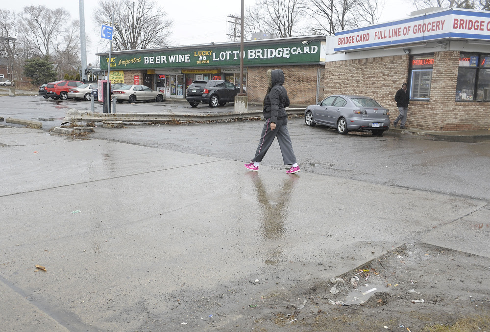 Cars enter local business at the scene of an attack on Wednesday at the street corners of Morang and Balfour on Thursday, April 3, 2014 in Detroit. A suburban Detroit man was in critical condition Thursday with severe head injuries after a neighborhood mob beat and kicked him when he stopped to check on a 10-year-old boy who stepped from a curb into the path of his pickup.