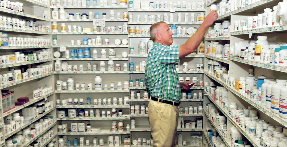 HIGH RISK: Kevin Holland, owner of Variety Pharmacy in Skowhegan, fills a prescription last week. Pharmacies, taxi companies and other businesses increasingly have become the target of robberies.