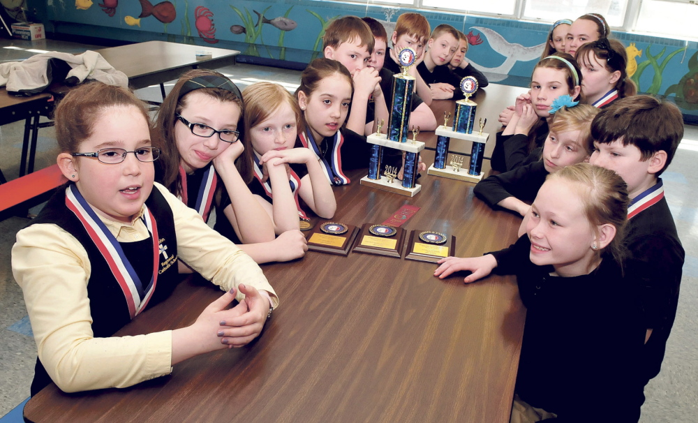 TEAM WORK: Student Dorothy Anne Giroux-Pare, left, and members of the St. John Catholic School Odyssey of the Mind team discuss going to the World Championship competition in Iowa this May at the Winslow school.