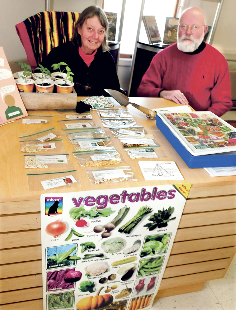 RETURN POLICY: Norridgewock Library Chairman of the Board Sallie Wilder and Librarian Kent Sinclair sit behind a display of seeds, information and gardening books last week. This is the second year of the seed program, where patrons with library cards can select packets of seeds and raise vegetable gardens at their homes.