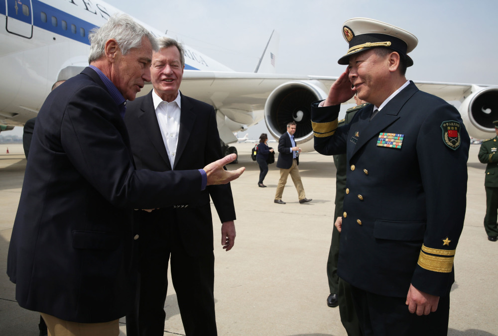 U.S. Secretary of Defense Chuck Hagel, left, is welcomed by Rear Admiral Guan Youfei, Director of Foreign Affairs Office of the Chinese Defense Ministry and U.S. Ambassador to China, Max Baucus, upon his arrival at Qingdao International Airport in Qingdao, China, on Monday.