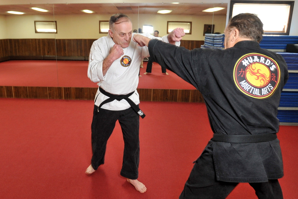 Staff photo by Michael G. Seamans Ron Raymond, 65, spars with Randy Huard at Huard's Jujitsu and Karate Gym in Winslow on Saturday.