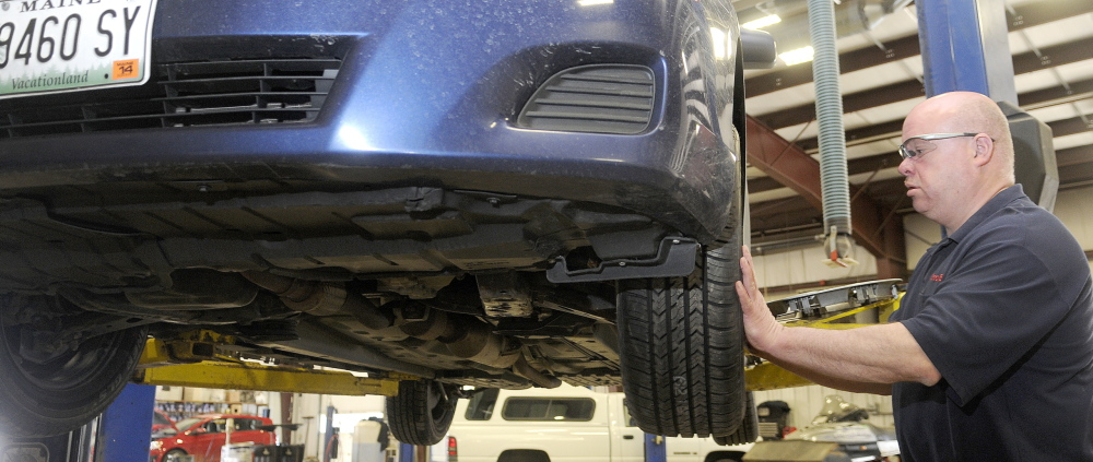 COSTLY SPRING: Dan Brooks mounts a tire Monday at his family's Augusta business, Capitol Car Care. The Brooks Boys car business has been busy this spring repairing vehicles that have sustained damaged from potholes, Brooks said.