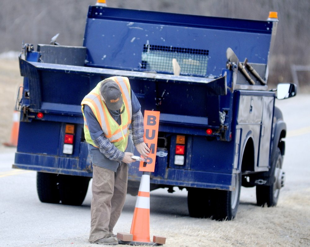ROUGH RIDE: Hallowell Public Works employee Scott Haskell posts a sign in front of a frost heave Monday on Vaughan Road. Haskell said the city had filled many potholes Monday but heaves are persisting this spring.