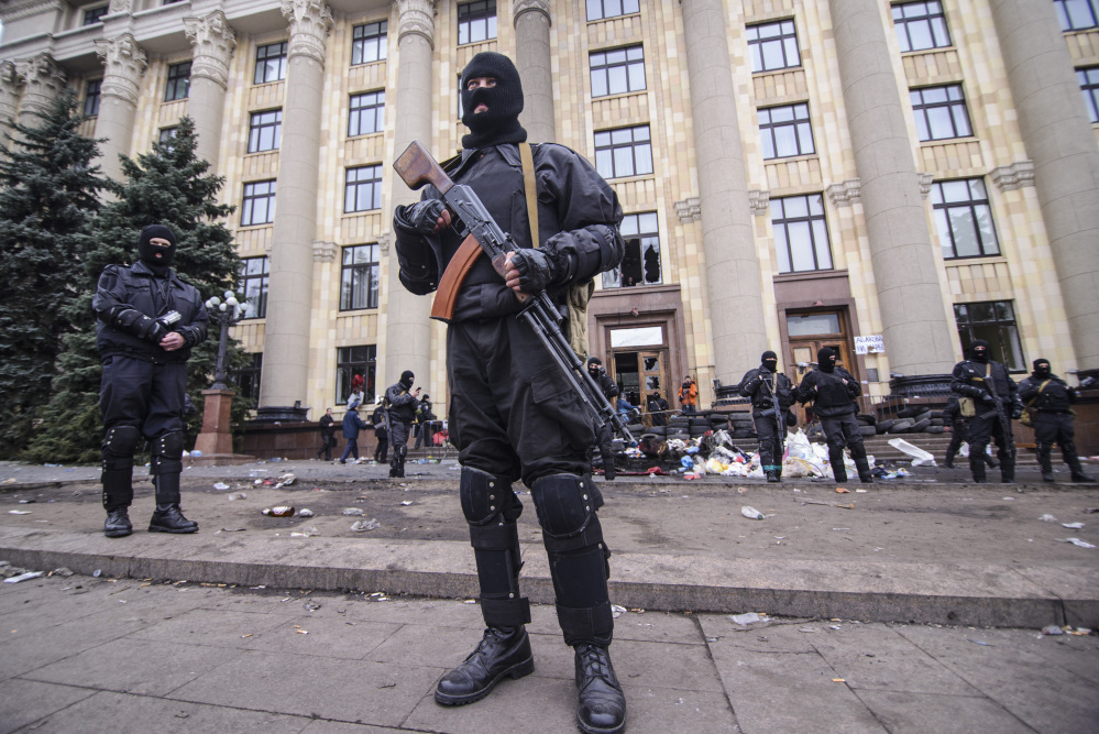 Members of a Special police unit guard the regional administration building in Kharkiv, Ukraine, Tuesday.