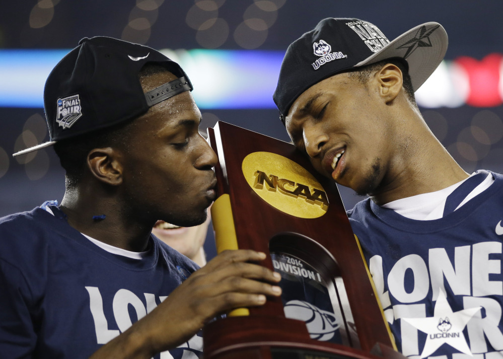 Connecticut guard Terrence Samuel, left, and guard Lasan Kromah hold the championship trophy after beating Kentucky 60-54, at the NCAA Final Four championship game on Monday in Arlington, Texas.