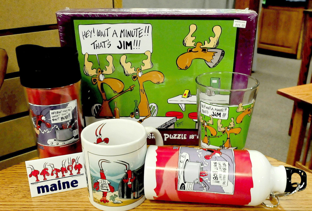 MAINE HUMOR: Magnets, coffee and drinking cups and a puzzle created by cartoonist Jeff Pert, of Winslow, are popular items sold at the Maine Made Shop in Waterville. Pert died on Friday.