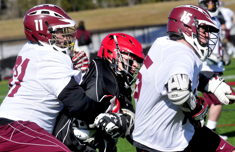 Staff photo by David Leaming Thomas College lacrosse player Parker Chute, center, is squeezed by University of Maine in Farmington players Jake Linkletter, left, and Connor Joy in Waterville on Wednesday, April 9, 2014.