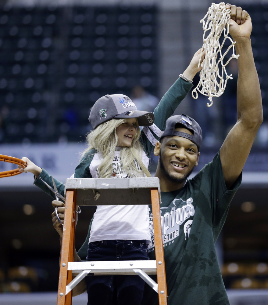 Michigan State forward Adreian Payne hoists the net with Lacey Holsworth after Michigan State defeated Michiganin an NCAA college basketball game.