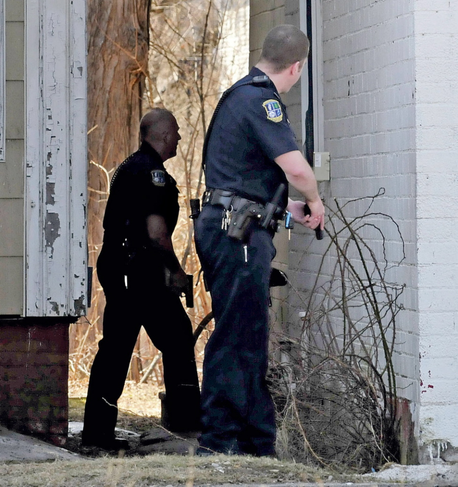 CAUTION: Waterville police officers Tim Hinton, left, and Damon Lefferts wait with their firearms drawn while calling out for Peter Corson who later came out and was arrested at 12 Spring St. in Waterville on Thursday.