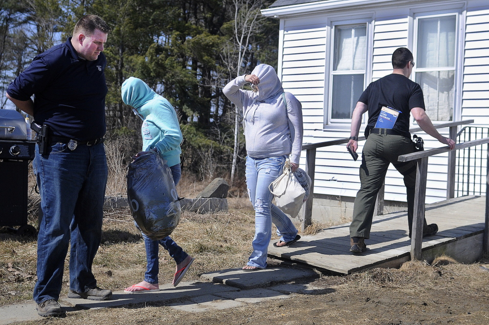 Raid: Women leave the residence Frederick Horne Sr. shares with his son, Frederick Horne Jr., in Sidney on Thursday after a raid by police. The Hornes were summoned on a charge of sex trafficking, with authorities saying at least a half-dozen women were at the home Thursday.