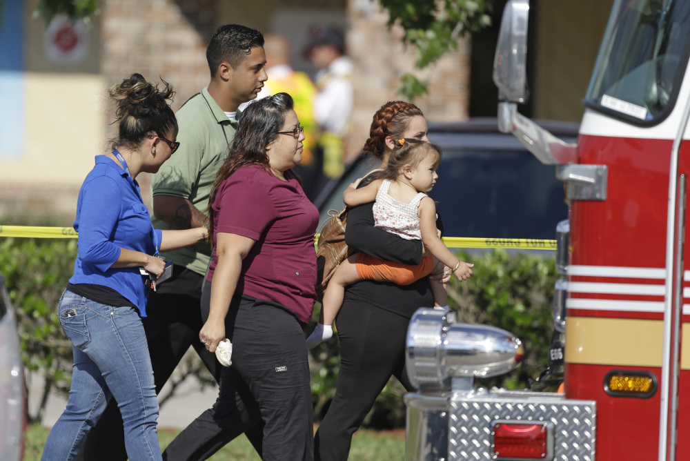Parents and relatives leave a day care center in Winter Park, Fla., with their children Wednesday after a vehicle crashed into the center, killing a girl and injuring 14 others, at least a dozen of them children, authorities said.