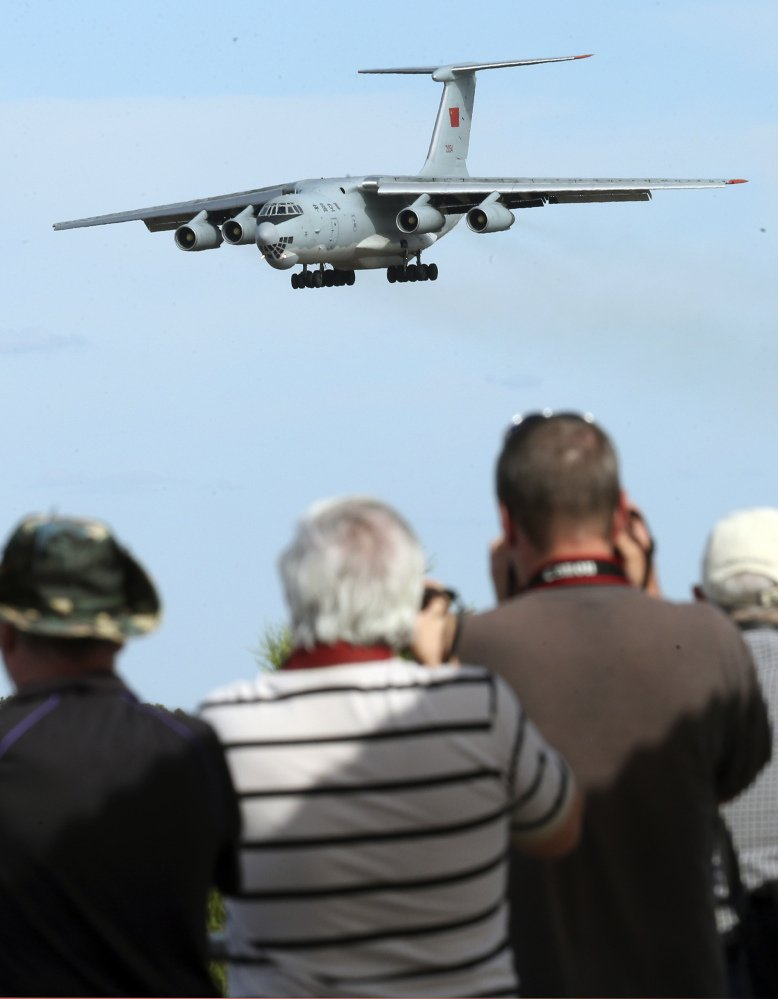 Spectators take photos of a Chinese Ilyushin IL-76 aircraft as it comes in for a landing at Perth International Airport after returning Thursday from the ongoing search operations for missing Malaysia Airlines Flight 370.