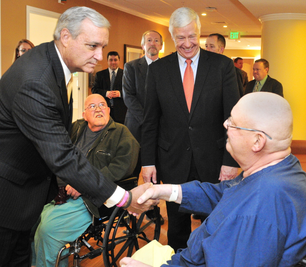 The chairman of the House Veterans' Affairs Committee Rep. Jeff Miller, R-Fla., left, shakes hands with Bruce Pray, of Winthrop, during a tour of the VA Maine Healthcare Systems-Togus on Friday. Pray and Donal Durgin, second from left, also of Winthrop, were chatting when Miller and Rep. Mike Michaud, D-2nd District, second from right, passed through.