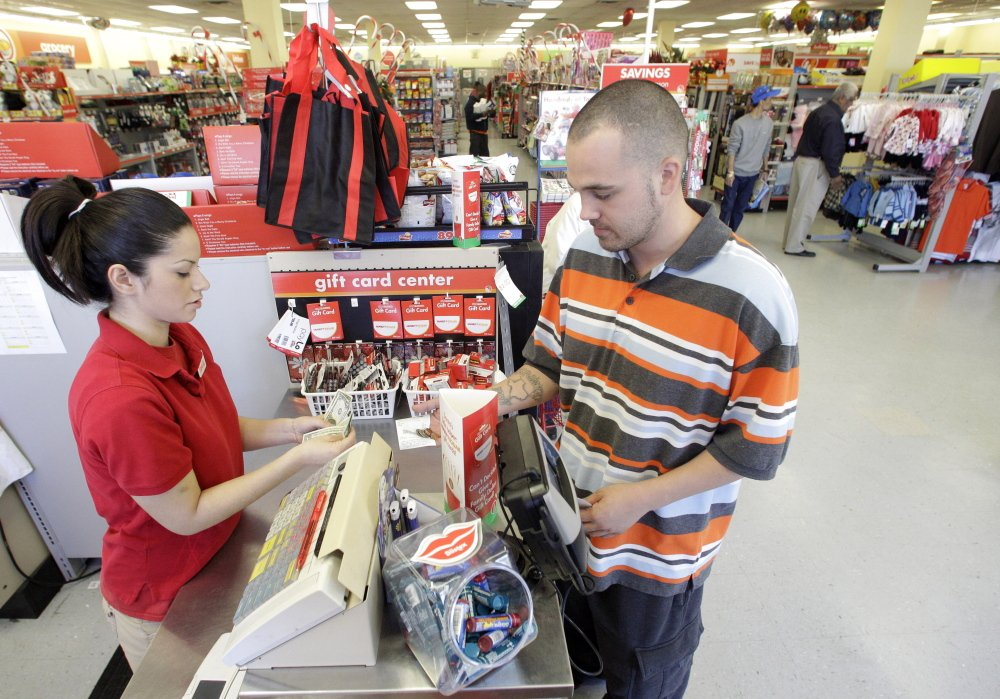 A Family Dollar employee assists a customer with a purchase at a store in Waco, Texas. Family Dollar on Thursday said it will be cutting jobs and closing about 370 underperforming stores.