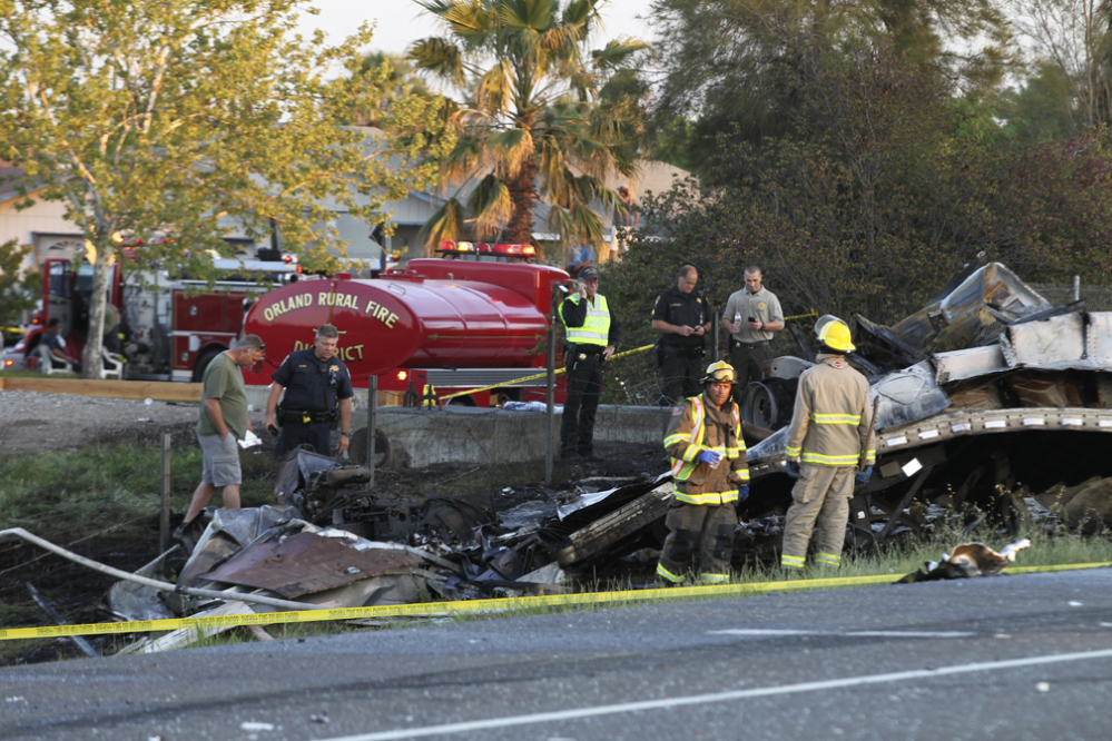 Firefighters hose down the wreckage of a bus and a semitruck that collided Thursday on Interstate 5 just north of Orland, Calif. Authorities said it is not yet clear what caused the crash.