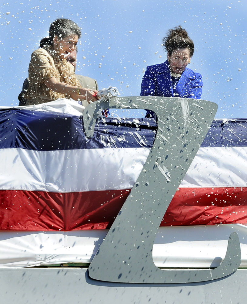 Admiral Elmo Zumwalt's daughters, Ann Zumwalt and Mouzetta Zumwalt-Weathers, break champagne bottles on a large letter Z during the christening of the USS Zumwalt at Bath Iron Works. Thousands witnessed Saturday's event celebrating the shipyard, the new warship and the memory of its namesake.