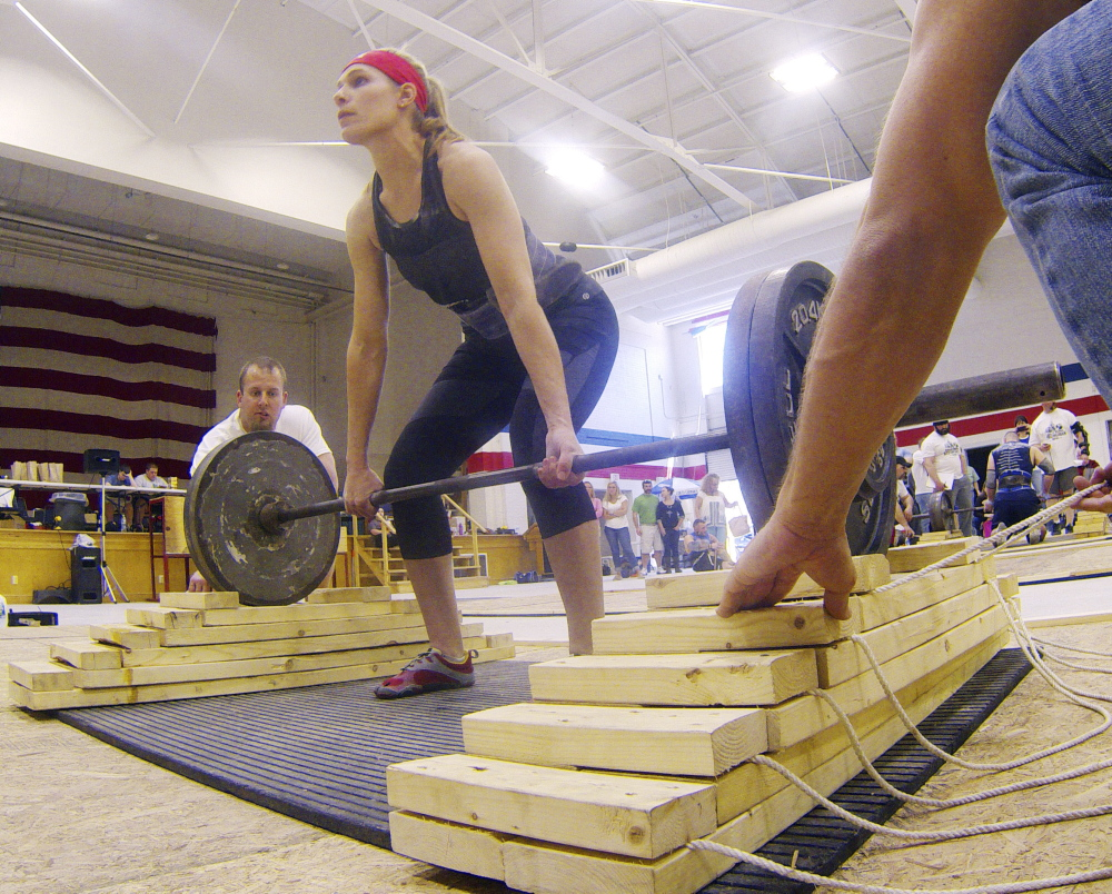 Strong Woman: Annie Philbrick, of Sidney, gets into position the women's novice division of descending dead lift during the Central Maine Strongman 7 competition on Saturday at Augusta Armory. Competitors have a minute to deadlift the weight as many reps as possible. A wooden support is pulled out with each lift, after they're all gone competitors keep lifting off the floor.